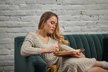 Blonde woman blogger in beige knitted dress and socks is sitting on gray sofa and reading book against white brick wall. Brown cup is nearby. Close-up