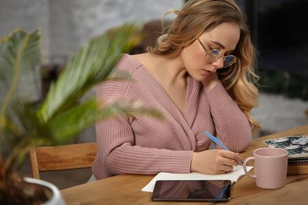 Girl in glasses, pink cardigan. Holding pen, sitting at wooden table with a tablet, notebook, cup and flower in pot on it. Student, blogger. Close-up