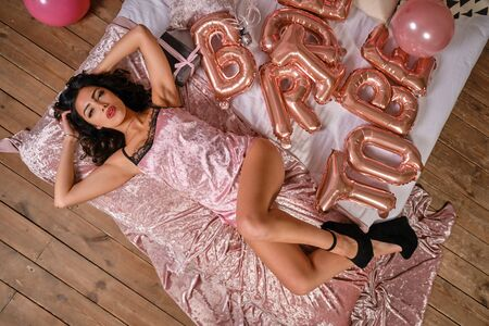 Alluring lady in pink lingerie is having fun during hen-party of bride, laying on bed. Studio with decorations, balloons. Close-up. Top view.