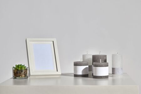 Table with green succulent in glass pot with sea pebbles, five different sized and colours candles, empty photo frame. Isolated on white. Interior design. Close up, copy space, mockup