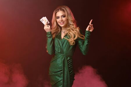 Blonde female in green dress, jewelry. Smiling, showing two aces, pointing at something, posing on colorful smoky background. Poker, casino. Close-up