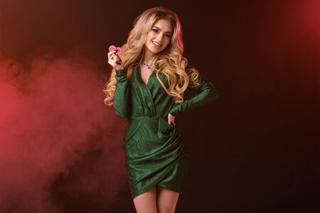 Gorgeous blonde lady in green stylish dress and jewelry. Smiling, showing two red chips, hand on waist, posing on colorful smoky background. Close-up