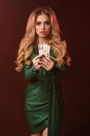 Blonde curly girl in green stylish dress and jewelry. She is showing two playing cards, posing on brown background. Poker, casino. Close-up