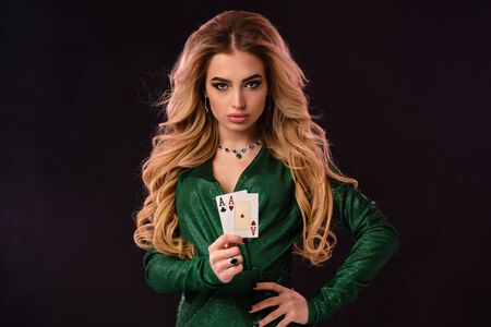 Blonde model in green stylish dress and jewelry. Put her hand on hip, showing two playing cards, posing on black background. Poker, casino. Close-up