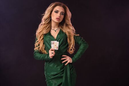 Blonde lady in green stylish dress and jewelry. Put her hand on hip, showing two playing cards, posing on black background. Poker, casino. Close-up Standard-Bild