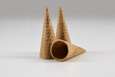 Three empty, sweet, medium wafer cones for ice cream isolated on white background. Concept of food and treats. Mockup, template for your advertising and design. Close up, copy space