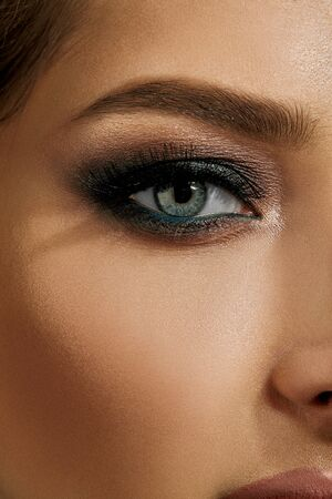 Face of lady with luxury makeup. Gray eyeshadow, long eyelashes, matte beige lips, brown eyebrows. Professional maquillage. Close up