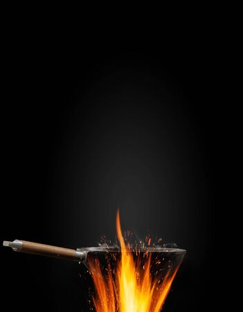 Empty wok pan with smoke above fire against black background. Cooking concept. Mockup, template for your collage, text, images. Advertising. Close up Фото со стока