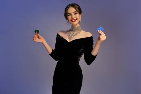 Brunette female in black dress and shiny jewelry. Smiling, showing two blue and green chips, posing on purple background. Poker, casino. Close-up