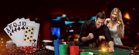Man and woman happy about win. Posing standing at playing table on colorful background. Winning combination in poker, stacks of chips. Casino