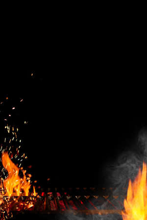 Empty barbecue BBQ grill with flaming fire and sparks, smoldering charcoal, smoke on black background. Close up, copy space