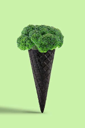 Ripe broccoli in a black wafer cone over light green background. Healthy nutrition, food and seasonal vegetables harvest. Close up, copy space