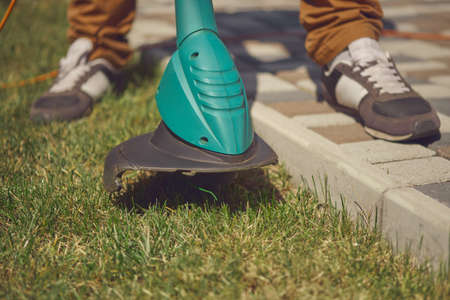 Male in sneakers and pants is cutting green grass with handheld modern lawn mower in his garden. Gardening care equipment and services. Close up 版權商用圖片
