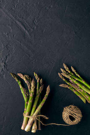 Ripe raw asparagus in bunch on black slate background. Tied with jute thread. Healthy nutrition, food and seasonal vegetables harvest. Close up 版權商用圖片