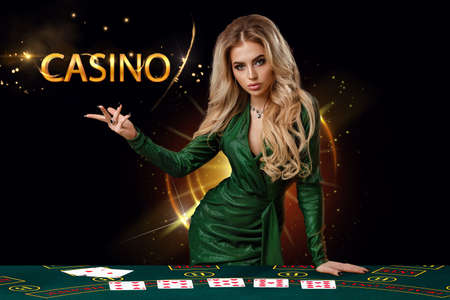 Lady in green dress is showing inscription casino, leaning on playing table with cards on it, posing on black background. Poker, casino. Copy space 版權商用圖片