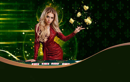 Blonde woman in red dress is showing golden flying suits of cards, leaning on playing table, posing on colorful background. Copy space. Poker, casino 版權商用圖片