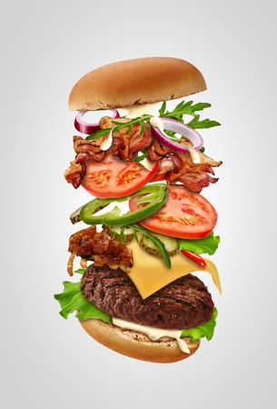 Big burger with flying ingredients against gray background. Ham, beef cutlet, cheese, mayonnaise, vegetables and greens. Close up, copy space 版權商用圖片