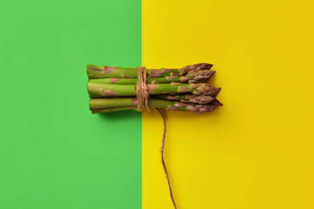 Green asparagus spears in bunch tied with jute thread over colorful background. Healthy nutrition, seasonal vegetables harvest. Close up, copy space 版權商用圖片 - 151849871