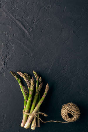 Uncooked green asparagus stems in bunch are tied with jute thread on black slate background. Skein is nearby. Seasonal vegetables harvest. Close up 版權商用圖片 - 151849771