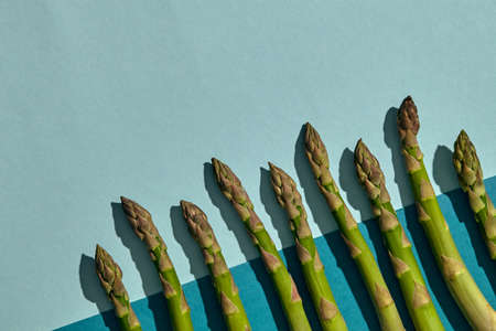 Ripe raw asparagus stalks on colorful background. Concept of healthy food and crop of spring vegetables. Close up, copy space