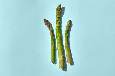 Three green asparagus spears on pink background. Concept of healthy food and seasonal vegetables harvest. Close up, copy space 版權商用圖片 - 151849773