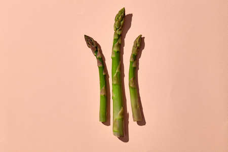 Three green asparagus spears on pink background. Concept of healthy food and seasonal vegetables harvest. Close up, copy space