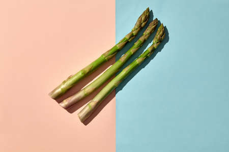 Three green asparagus spears on colorful background. Concept of healthy nutrition, food and seasonal vegetables harvest. Close up, copy space 版權商用圖片 - 151849782