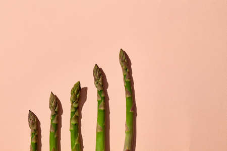 Asparagus stems against pink background. Concept of healthy nutrition, food and seasonal vegetables harvest. Close up, copy space 版權商用圖片 - 151849783