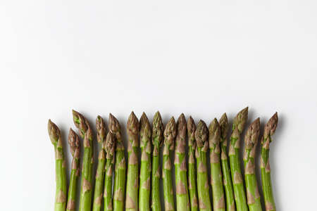 Green fresh asparagus stems isolated on white background. Healthy nutrition, food and seasonal vegetables harvest. Close up, flat lay, top view
