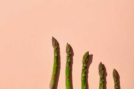 Organic green asparagus spears on pink background. Healthy nutrition, food and seasonal vegetables harvest. Close up, flat lay, top view