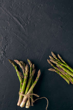 Green asparagus in bunch on black slate background. Tied with jute thread. Healthy nutrition, food and seasonal vegetables harvest. Close up