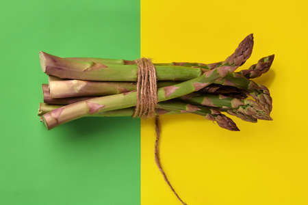 Green asparagus sprouts in bunch tied with jute thread over colorful background. Healthy nutrition, seasonal vegetables harvest. Close up, copy space