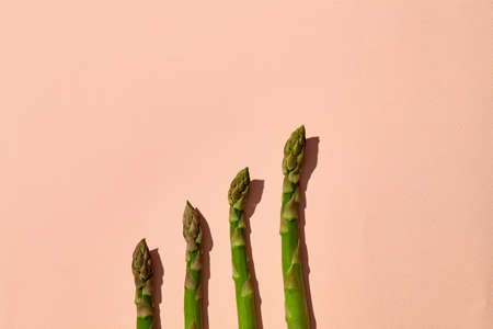 Ripe green asparagus stalks on pink background. Healthy nutrition, food and seasonal vegetables harvest. Close up, flat lay, top view