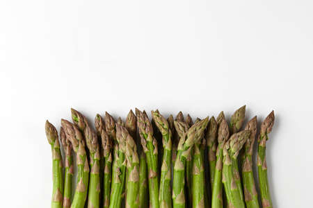 Green raw asparagus spears isolated on white studio background. Healthy nutrition, food and seasonal vegetables harvest. Close up, flat lay, top view 版權商用圖片