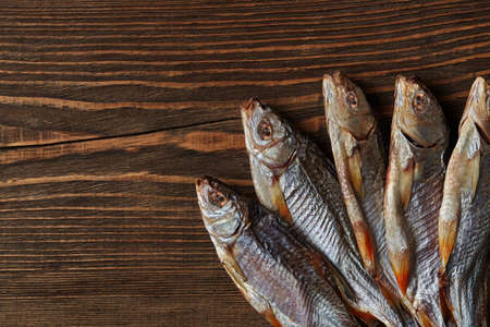 Dried or jerky salted roach, clipfish on wooden background. Salty beer appetizer. Traditional way of preserving fish. Close up 版權商用圖片