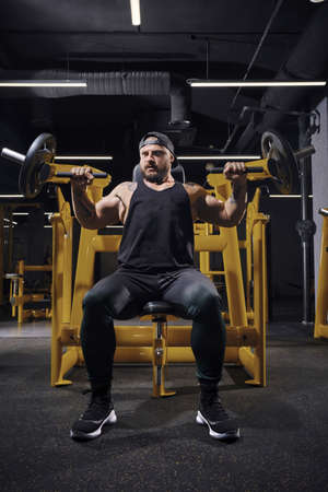 Tattooed, bearded, strong guy in black sweatpants, vest and cap. He performing chest press, sitting on an exercise machine at dark gym. Full length