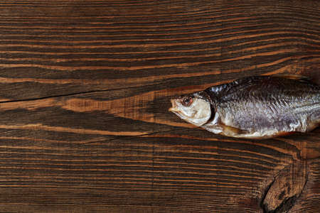 One dried or jerky salted roach, tasty clipfish on wooden background. Salty beer appetizer. Traditional way of preserving fish. Close up 版權商用圖片