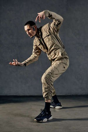 Flexible performer with tattooed body, earrings, beard. Dressed in khaki overalls and black sneakers. Dancing on gray background. Dancehall, hip-hop