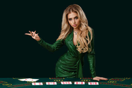 Girl in stylish dress is showing something, leaning on playing table with cards on it, posing on green background. Poker, casino. Close-up, copy space Standard-Bild