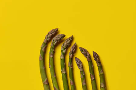 Ripe uncooked green asparagus spears against yellow background. Healthy nutrition, food and seasonal vegetables. Close up, flat lay, top view