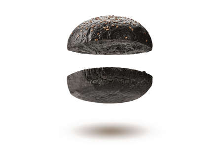 Flying, baked or grilled, cut in half black burger bun with sesame seeds isolated on white background. Cooking, fast food. Close-up, copy space 版權商用圖片