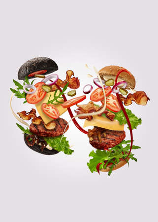 Two burgers, black and classic, with flying ingredients against gray background. Ham, beef cutlet, cheese, sauces, vegetables and greens. Close up