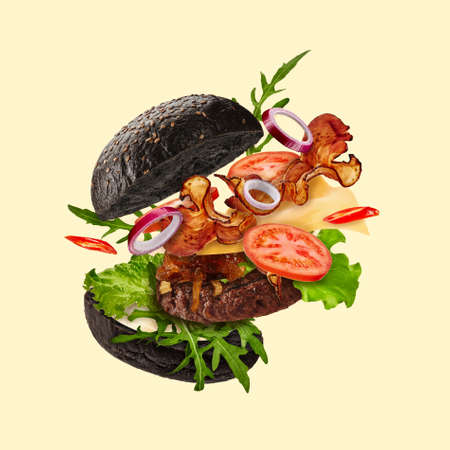 Fresh black burger with flying ingredients on beige background. Ham, beef cutlet, cheese, sauces, vegetables and greens. Close up, copy space