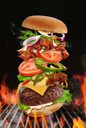 Big hamburger roasted on barbecue BBQ grill with bright flaming fire against black background. Beef cutlet, ham, cheese, vegetables and greens 版權商用圖片 - 155264568