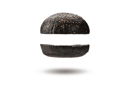 Flying and delicious, baked or grilled, two halves of black burger bun with sesame seeds. Isolated on white. Cooking, fast food. Close-up, copy space 版權商用圖片