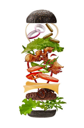 Big black burger with flying ingredients isolated on white background. Ham, beef cutlet, cheese, mayonnaise, ketchup, vegetables and greens. Close up