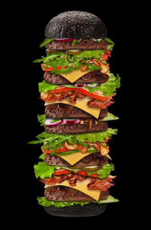 Huge appetizing black burger on black background. Ham, beef cutlet, cheese, vegetables and greens. Cooking and fast food. Close up, copy space 版權商用圖片