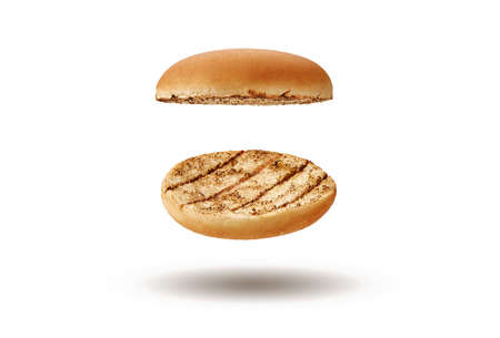Flying and palatable, baked or grilled, two halves of burger bun isolated on white background. Concept of cooking and fast food. Close-up, copy space 版權商用圖片