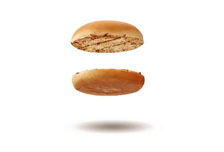 Flying and appetizing, baked or grilled, cut in half burger bun isolated on white background. Concept of cooking and fast food. Close-up, copy space