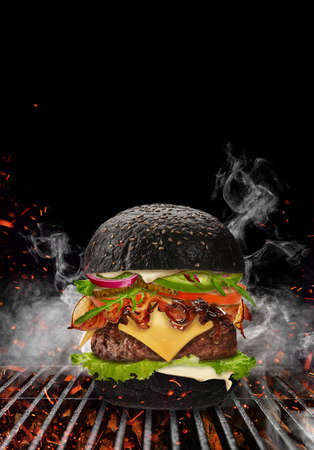 Black burger roasted on barbecue grill with flaming fire, sparks and smoke against black background. Beef cutlet, ham, cheese, vegetables and greens